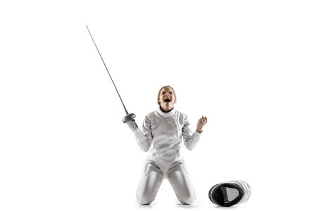 Close up of teen girl in fencing costume with sword in hand isolated on white studio background. Young female model in motion, action. Celebrating win emotional. Sport, youth, healthy lifestyle. Stockfoto