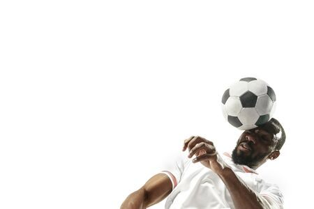 Close up of emotional african man playing soccer hitting the ball with the head on isolated white background. Football, sport, facial expression, human emotions, healthy lifestyle concept. Copyspace.