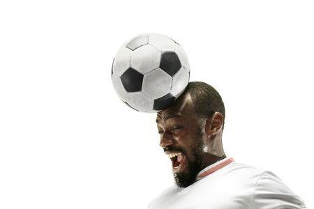 Cerca del hombre africano emocional jugando al fútbol golpeando la pelota con la cabeza sobre fondo blanco aislado. Fútbol, deporte, expresión facial, emociones humanas, concepto de estilo de vida saludable. Copyspace.