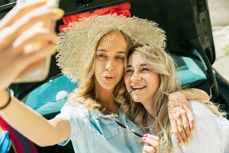 Young lesbians couple preparing for vacation trip on the car in sunny day. Smiling and happy girls before going to sea or ocean. Concept of relationship, love, summer, weekend, honeymoon, vacation.