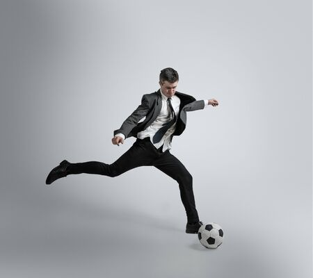 Dream about the biggest win in life. Man in office clothes traines in football or soccer with ball on grey background. Unusual look for businessman in motion, action. Sport, healthy lifestyle. Banco de Imagens