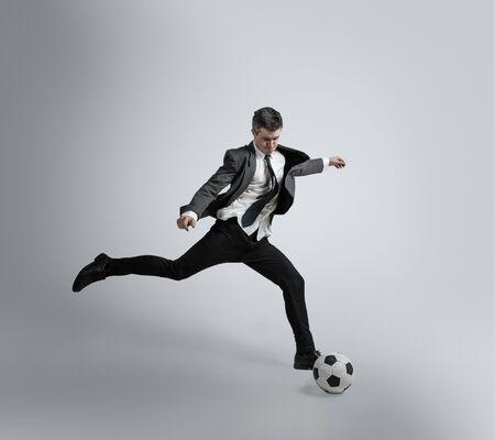 Rêve de la plus grande victoire de la vie. L'homme en vêtements de bureau s'entraîne au football ou au soccer avec ballon sur fond gris. Look inhabituel pour homme d'affaires en mouvement, action. Sport, mode de vie sain. Banque d'images
