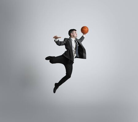 Back in college - its never too late for being sport star. Man in office clothes traines in basketball on grey background. Unusual look for businessman in motion, action. Sport, healthy lifestyle.