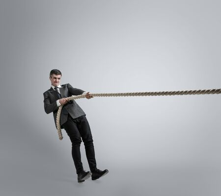 Time for strenght. Man in office clothes training with ropes on grey background. Get target, overcoming problems, deadlines. Businessman in motion, action. Sport, healthy lifestyle, working. Stock Photo