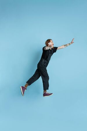 Portrait of young caucasian man looks dreamful, cute and happy. Jumping. laughting on blue studio background. Copyspace for your advertising. Concept of future, target, dreams, visualisation. Zdjęcie Seryjne
