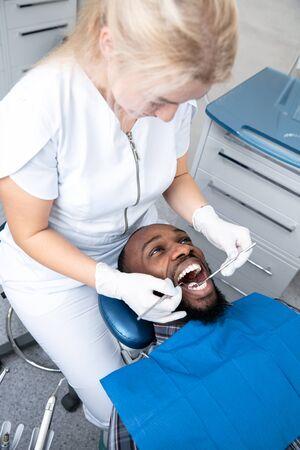 Jeune homme afro-américain visitant le cabinet du dentiste pour la prévention et le traitement de la cavité buccale. Homme et femme médecin lors de l'examen des dents. Concept de mode de vie sain, de soins de santé et de médecine.