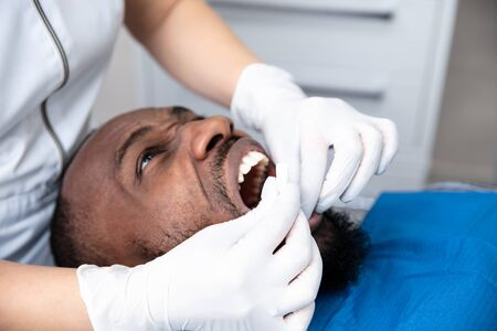 Young african-american man visiting dentist's office for prevention and treatment of the oral cavity. Man and woman doctor while checkup teeth. Healthy lifestyle, healthcare and medicine concept.