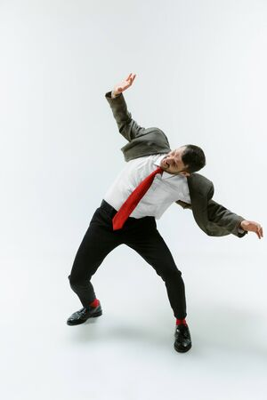Young caucasian man moving flexible on white studio Stock Photo