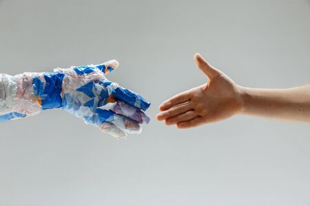 Big plastic hand made of garbage shaking another hand on white studio Foto de archivo