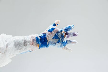 Big plastic hand made of garbage isolated on white studio background. The result of polymers overusing and overproduction. Ecology problems, pollution, recycling. It's getting dangerous for humanity.