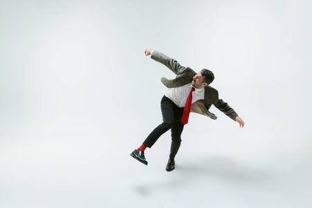 Junger kaukasischer Mann, der sich flexibel auf weißes Studio bewegt Standard-Bild