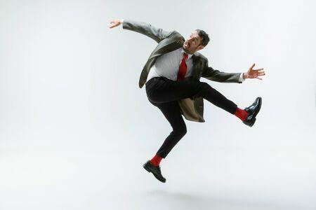 Hombre caucásico joven moviendo flexible en estudio blanco