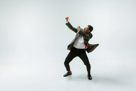 Young caucasian man moving flexible on white studio