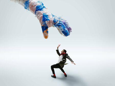 Young caucasian man avoiding big plastic hand on white studio