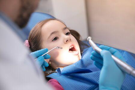 Jeune fille caucasienne calme et heureuse en visite chez le dentiste pour la prévention et le traitement de la cavité buccale. Enfant et médecin lors de l'examen des dents. Concept de mode de vie sain, de soins de santé et de médecine.