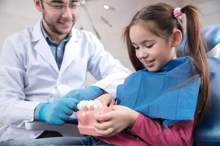 Young caucasian girl exploring teeth structure visiting dentists office for prevention of the oral cavity. Child and doctor while checkup teeth. Healthy lifestyle, healthcare and medicine concept.