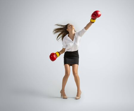 When its getting you up. Woman in office clothes boxing in gloves on grey studio background. Businesswoman training in motion, action. Unusual look for sport, new activity. Sport, healthy lifestyle.