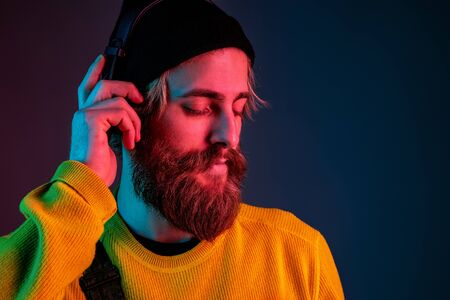 Calm, happy. Caucasian mans portrait on gradient studio background in neon light. Beautiful male model with hipster style in earphones. Concept of human emotions, facial expression, sales, ad.