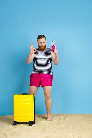 Dream comes true. Happy young man with bag prepared for traveling on blue studio background. Concept of human emotions, facial expression, summer holidays, weekend. Summertime, sea, ocean, alcohol.