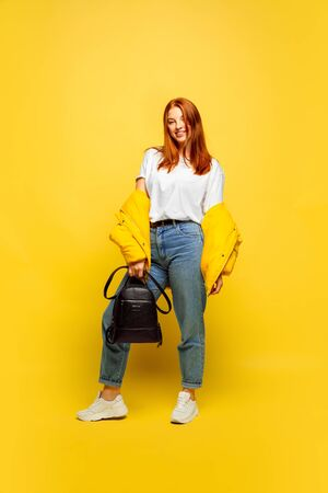 Its easier to be follower. Need minimum clothes to go. Caucasian womans portrait on yellow background. Beautiful female red hair model. Concept of human emotions, facial expression, sales, ad.