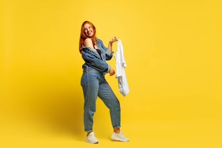 Its easier to be follower. Laundry faster, if its only one shirt. Caucasian womans portrait on yellow background. Beautiful red hair model. Concept of human emotions, facial expression, sales, ad.