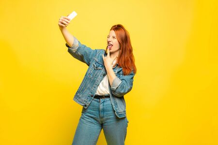 Its easier to be follower. Need minimum clothes for selfie. Caucasian womans portrait on yellow background. Beautiful female red hair model. Concept of human emotions, facial expression, sales, ad. Imagens