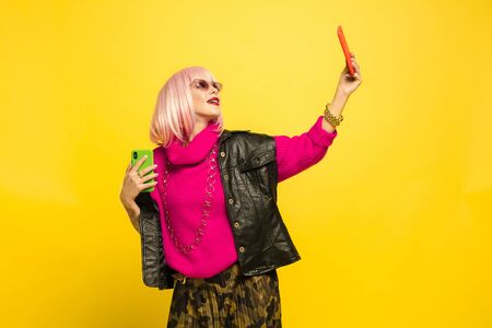 Its hard to be influencer. Selfie only in special clothes and make up. Caucasian womans portrait on yellow background. Beautiful blonde model. Concept of human emotions, facial expression, sales, ad.