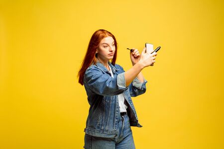 Its easier to be follower. Need no selfie for make up. Caucasian womans portrait on yellow background. Beautiful female red hair model. Concept of human emotions, facial expression, sales, ad. Banco de Imagens
