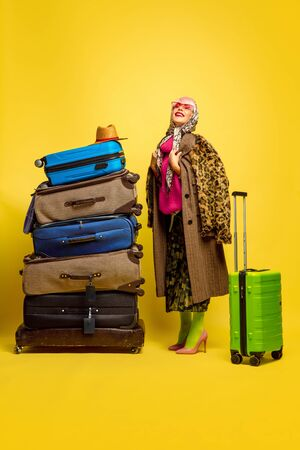 It's hard to be influencer. A lot of clothes for travel to go. Caucasian woman's portrait on yellow background. Beautiful blonde model. Concept of human emotions, facial expression, sales, ad. Stock Photo