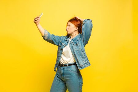 Its easier to be follower. Need minimum clothes for selfie. Caucasian womans portrait on yellow background. Beautiful female red hair model. Concept of human emotions, facial expression, sales, ad. Banco de Imagens