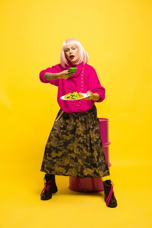 Its hard to be influencer. Selfie first, eating later. Need shot a dish before. Caucasian womans portrait on yellow. Beautiful blonde model. Concept of human emotions, facial expression, sales, ad. Stock Photo