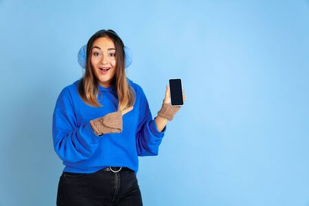 Showing blank screen. Caucasian womans portrait on blue studio background. Beautiful female model in warm clothes. Concept of human emotions, facial expression, sales, ad. Winter mood.