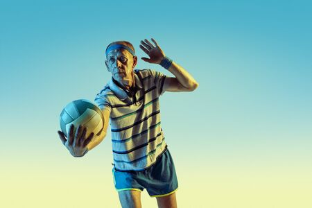 Senior man wearing sportwear playing volleyball on gradient background, neon light. Caucasian male model in great shape stays active. Concept of sport, activity, movement, wellbeing, confidence.