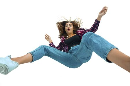 A second before falling. Caucasian young girl falling down in moment with bright emotions and facial expression. Female model in casual clothes. Shocked, scared, screaming. Copyspace for ad. Stock Photo