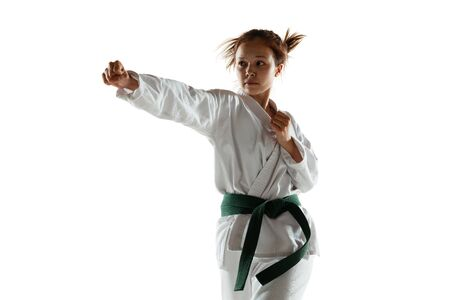 Confident junior in kimono practicing hand-to-hand combat, martial arts. Young female mongol fighter with green belt training on white studio background. Concept of healthy lifestyle, sport, action. Stock Photo