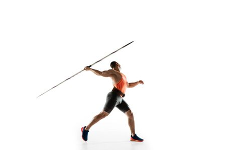 Male athlete practicing in throwing javelin isolated on white studio background. Professional sportsman training in motion, action. Concept of healthy lifestyle, movement, activity. Copyspace. Standard-Bild