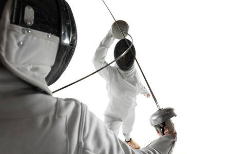 Teen Mädchen in Fechtkostümen mit Schwertern in den Händen isoliert auf weißem Studiohintergrund. Junge weibliche Modelle üben und trainieren in Bewegung, Aktion. Exemplar. Sport, Jugend, gesunder Lebensstil.