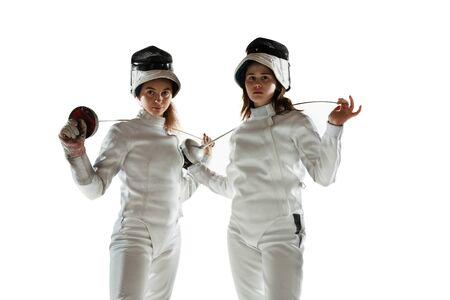 Confiance. Adolescentes en costumes d'escrime avec des épées en mains sur fond blanc. Jeunes modèles féminins pratiquant et s'entraînant en mouvement, action. Espace de copie. Sport, jeunesse, mode de vie sain. Banque d'images
