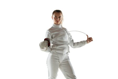 Champion. Teen girl in fencing costume with sword in hand isolated on white background. Young female model practicing and training in motion, action. Copyspace. Sport, youth, healthy lifestyle.