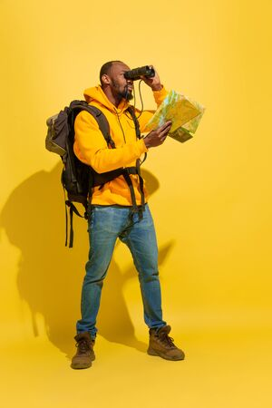 Looking forward. Portrait of a cheerful young african-american tourist guy with bag and binoculars isolated on yellow studio background. Preparing for traveling. Resort, human emotions, vacation.