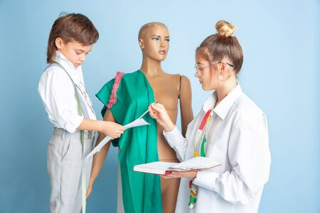 Creature. Little boy and girl dream about profession of seamstress. Childhood, education and dream concept. Want to become successful in fashion and style industry, atelier, make clothes. Copyspace. Stockfoto