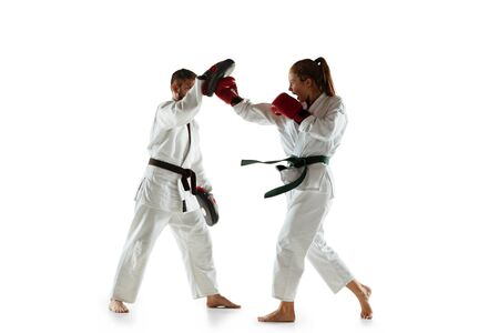 Junior in kimono practicing hand-to-hand combat with coach, martial arts. Young female mongol fighter with green belt training on white studio background. Concept of healthy lifestyle, sport, action.