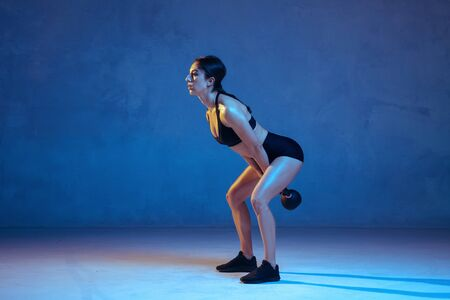 Caucasian young female athlete practicing on blue studio background in neon light. Sportive model training her lower body with weights. Body building, healthy lifestyle, beauty and action concept.