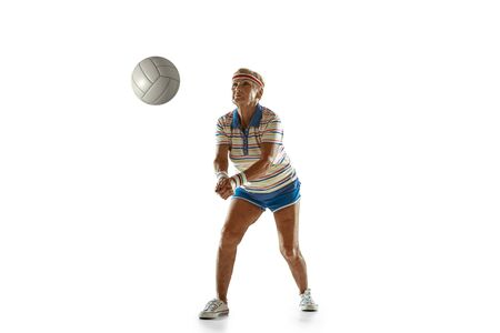 Senior woman wearing sportwear playing volleyball on white background. Caucasian female model in great shape stays active. Concept of sport, activity, movement, wellbeing, confidence. Copyspace.