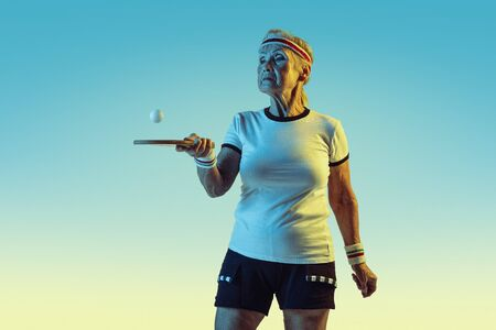 Senior woman in sportwear training in table tennis on gradient background, neon light. Female model in great shape stays active. Concept of sport, activity, movement, wellbeing, confidence. Copyspace.