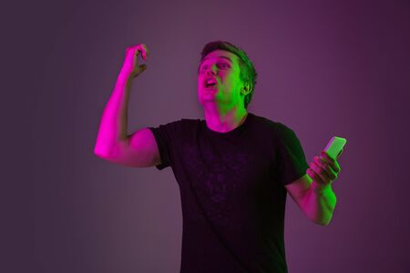 Using smartphone, betting, winning. Caucasian man's portrait on purple studio background in neon light. Beautiful male model in black shirt. Concept of human emotions, facial expression, sales, ad. Stock Photo
