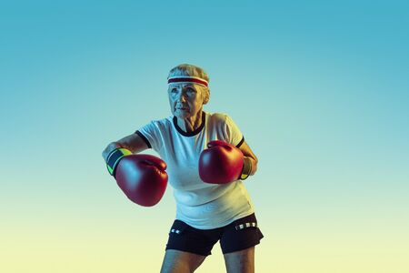 Still kicking. Senior woman in sportwear boxing on gradient background, neon light. Female model in great shape stays active. Concept of sport, activity, movement, wellbeing, confidence. Copyspace.
