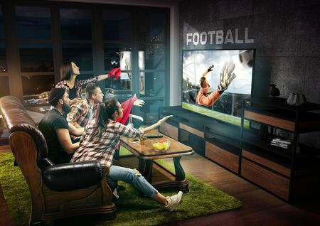 Group of friends watching TV, football match, leisure activity. Emotional men and women cheering for favourite team, look on fighting for ball. Concept of friendship, sport, competition, emotions.