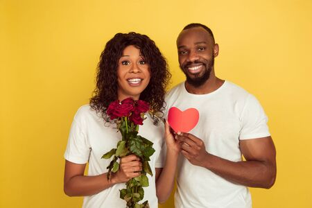 Flowers and heart. Valentines day celebration, happy african-american couple isolated on yellow studio background. Concept of human emotions, facial expression, love, relations, romantic holidays.