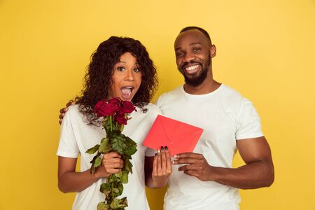 Roses and red envelope. Valentines day celebration, happy african-american couple isolated on yellow studio background. Concept of human emotions, facial expression, love, relations, romantic holidays. Stok Fotoğraf